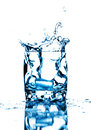 Ice cube splashing into glass of water Royalty Free Stock Photo