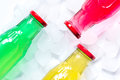 Ice cubes and bright bottles on white background top view mock up