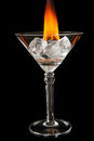 Ice cubes in glass with flame on shiny black surface melting Royalty Free Stock Photo