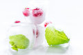 Ice cubes with red berries and mint white background