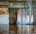 Ice cycles on the boardwalk in the water as the tide rises Stock Photos