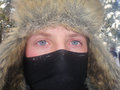 Ice eyes closeup of face of male teenager with furry hat and balaclava blue with frost crystals Stock Image