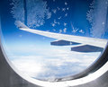 Ice flowers on airplane window with wings in background Royalty Free Stock Photos