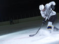 Ice hockey player in action kicking with stick Stock Image