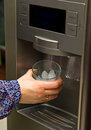 Ice making fridge female hand holding a glass at Royalty Free Stock Photography