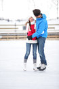 Ice skating couple on date in love iceskating and embracing young embracing skates outdoors open air rink Royalty Free Stock Image