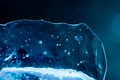 Ice texture closeup. Frozen water and air bubbles. Transparent abstract shape object on cold blue winter background Royalty Free Stock Photo