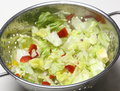 Iceberg lettuce salad with red peppers chopped and being washed in a metal colander Stock Photography