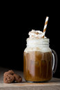 Iced coffee in a mason jar with whipped cream and brown striped glass shallow depth of field black background with copy space on Royalty Free Stock Photography