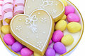 Iced heart shaped cookies two on a plate with sugared almonds Royalty Free Stock Photo