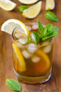 Iced tea with lemon and mint on a wooden background Royalty Free Stock Photos
