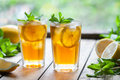 Iced tea with lemon slices and mint on wooden table with a view to the terrace and trees. Close up summer beverage Royalty Free Stock Photo