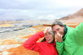 Iceland funny tourists selfie at mudpot hot spring couple having fun taking photo with landmark destination namafjall hverarondor Stock Photo