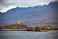 Iceland sea mountains landscape orange lighthouse horizontal shot Royalty Free Stock Photo