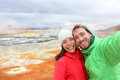 Iceland tourists selfie at mudpot hot spring couple taking photo with smartphone camera landmark destination namafjall hverarondor Royalty Free Stock Image