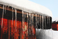 Icicle and snow on the roof cold season snowdrift of a country wooden house in winter blue sky background Royalty Free Stock Photo