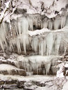 Icicles hang in neat rows on the background of rocks Stock Image