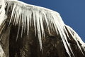 Icicles hang on the rock with blue sky. Royalty Free Stock Photo