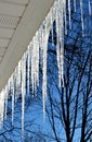 Icicles hanging from the edge of roof Stock Photos