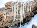 Icicles hanging from a rock frozen are in winter Royalty Free Stock Photos