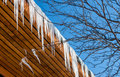 Icicles and roof hanging from a wooden in winter Stock Photos