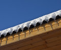 Icicles are on the roof of a wooden house a background of blue sky Royalty Free Stock Images