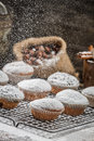 Icing sugar falling on fresh vanilla muffins old wooden table Royalty Free Stock Image