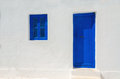 Iconic blue wooden door and window against clear white wall. Royalty Free Stock Photo
