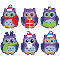 Icons in the form of colorful owls in winter hats on a white background Royalty Free Stock Photo