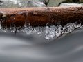 Icy branches above  chilling stream. Reflections in icicles Royalty Free Stock Photo