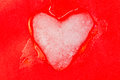 Icy heart melts with love ice cold made ​​of snow on a red background Royalty Free Stock Images
