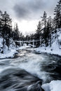 Icy river flowing under the bridge Stock Photos