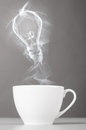 Idea birth bulb silhouette from steaming hot coffee cup Stock Image