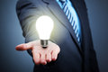 Idea businessman with illuminated light bulb balancing on his hand concept for innovation and inspiration Royalty Free Stock Photos
