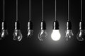 Idea concept with broken bulbs and one glowing bulb Royalty Free Stock Photos