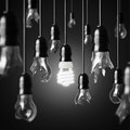Idea concept with broken bulbs and one glowing energy saving bulb Stock Images