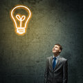 Idea concept young thoughtful businessman looking above at light bulb Stock Images