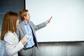 Idea confident businessman pointing at whiteboard while making speech with smart secretary near by Stock Photos