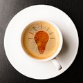 Idea cup of fresh espresso with bulb sign view from above Stock Photos