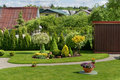 Ideal european garden part of an decorative rural with a green lawn flowers and bushes sunny day summer landscape Stock Photos