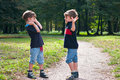 Identical twin brothers cheering on a forest trail three four year old boys they express delight children wear orthopedic shoes Royalty Free Stock Images