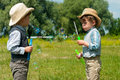 Identical twins blow soap bubbles three year old on the meadow Stock Photography