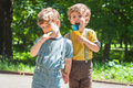 Identical twins eat lollies Royalty Free Stock Photo