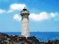 Idle lighthouse before blue sea and fluffy clouds Stock Images