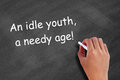 An idle youth a needy age written on blackboard Royalty Free Stock Photography
