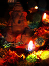 An idol of lord ganesh being worshipped with a traditional lamp and flowers Stock Photos