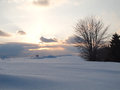 Idylic sunset at a winter snowy field in the twilight