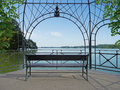 Idyllic lakeside pavilion park bench in a romantic by a beautiful lake Royalty Free Stock Image