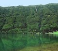 Idyllic lakeside scenery translucent lake and overgrown hills at sao miguel island the biggest island of the azores archipelago a Royalty Free Stock Image