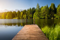 Idyllic view of the wooden pier in the lake with mountain scenery background Royalty Free Stock Photo